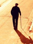 Old man walking on road