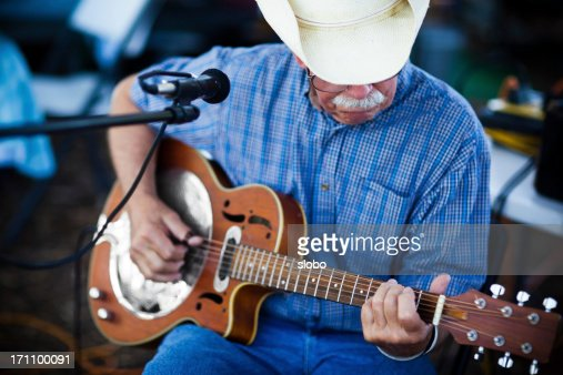 old man with cowboy hat playing blues on a guitar outdoors