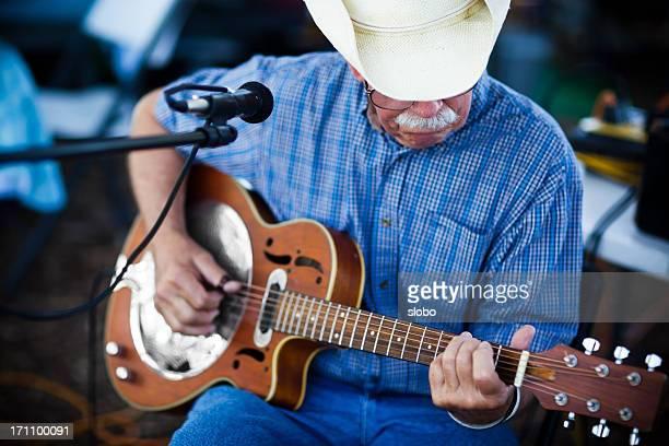 Vieil homme avec Chapeau de cow-boy joue sur une guitare blues à l'extérieur