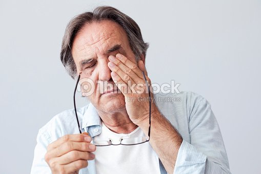 Old man with eye fatigue : Stock Photo