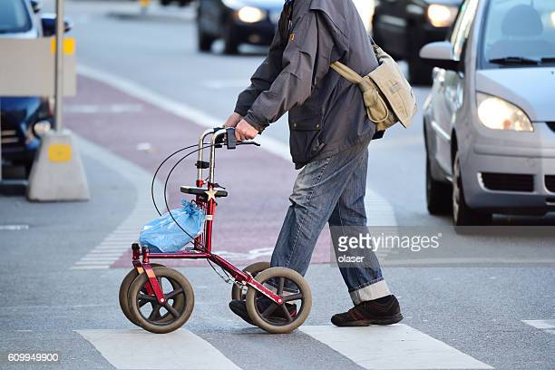 Old man with walking support rollator on zebra crossing
