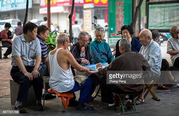 Old men play mahjong on the street In China there are more than 200 million old people of over 60 years old at present which accounts for 15% of...