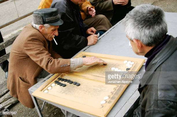 Old men playing backgamon on the streets April 29 2004 in the town of Stepanakert in the Askeran Province of NagornoKarabakh Azerbaijan These men...