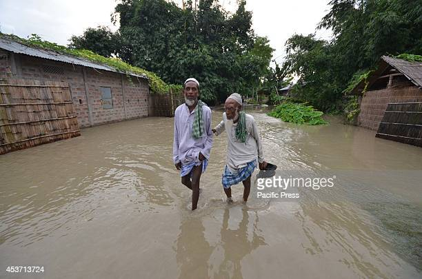 Old men walk through flood waters to a higher place after waters of the River Barhmaputra entered their houses at Bhurbandha in Nagaon district of...