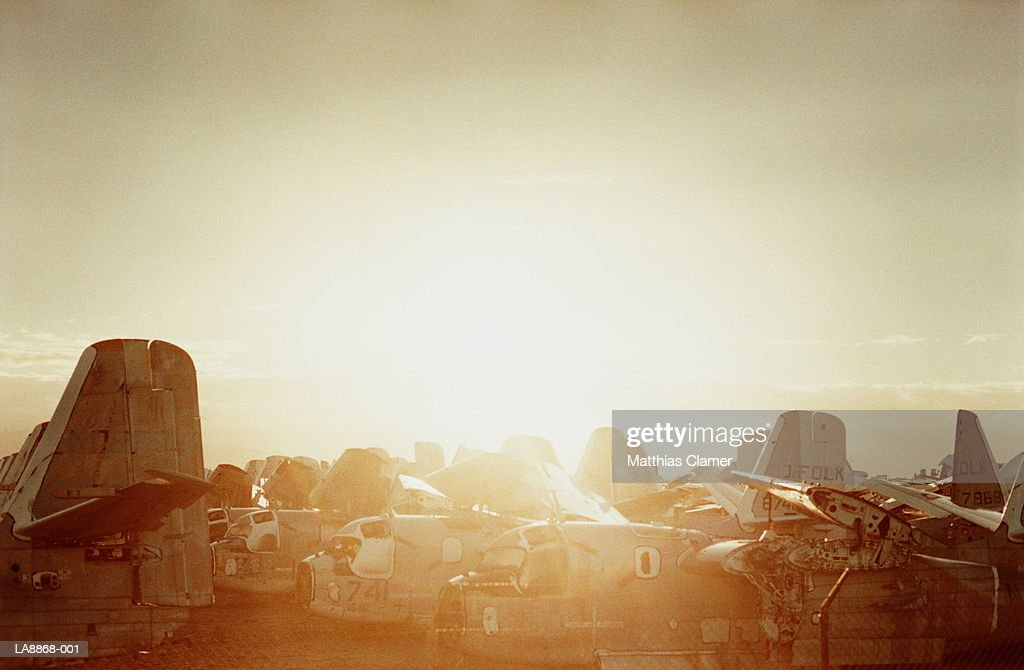 Old military aircraft in storage, sunrise : Stock Photo