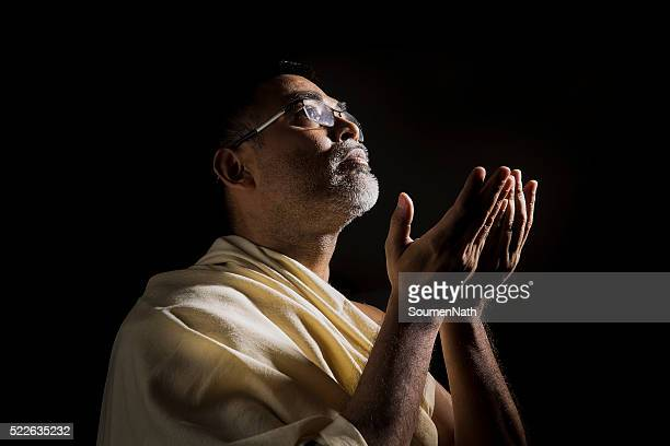Old Muslim man praying with folded hands