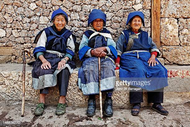 Old Naxi women sitting in street in village near Lijiang.