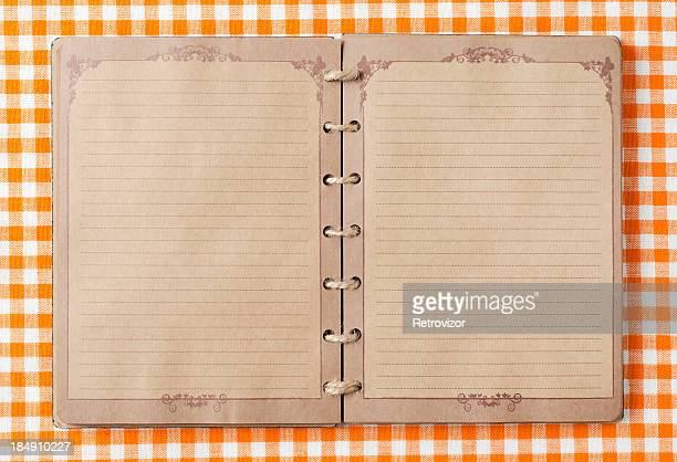 Old notebook on orange tableclot