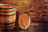 Old oak barrels on the brick wall backgroung.