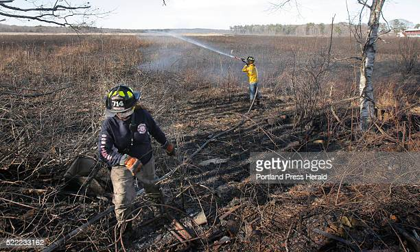 Old Orchard Beach firefighter Corey Pelletier walks back into the woods from a marsh in Old Orchard Beach where Saco firefighter Joe Demers sprays...