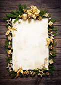 Old paper bordering with christmas decoration on wooden background