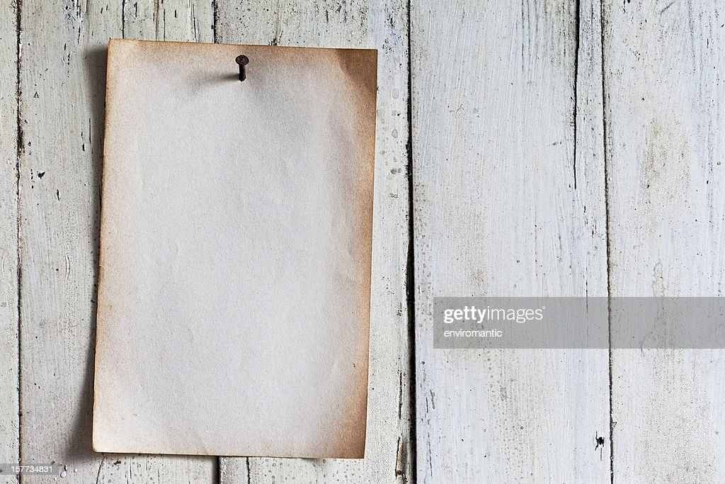 Old paper nailed to a weathered wooden board. : Stock Photo