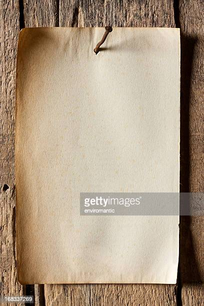Old paper nailed to a weathered wooden board.