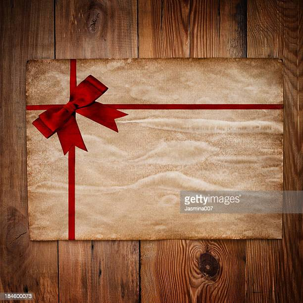 Old paper  with red ribbon on  wooden wall