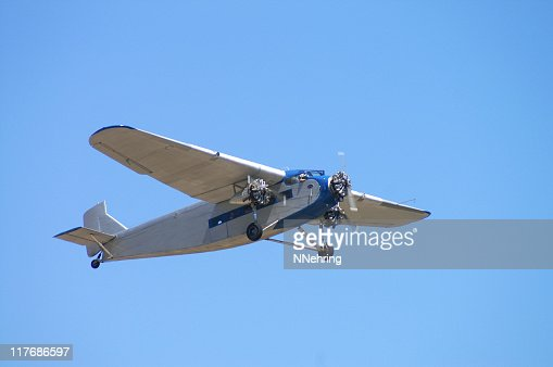 old passenger airplane Ford Trimotor flying in clear blue sky