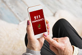 Unrecognisable old person dialing emergency number 911 on phone