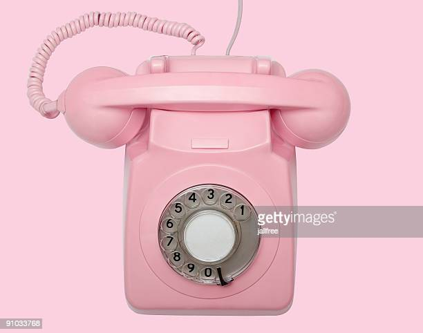 Old pink telephone on pink background with path