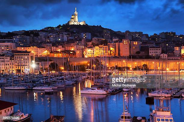 Old Port harbour or Vieux Port, Marseille, France, Europe at night with view of the Notre Dame de la Garde on the hill