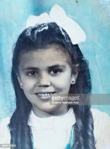 Old portrait of young girl with bow in her hair smiling at the camera Cuban lifestyle in the early decades of the XX century