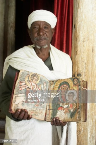 Old priest with illuminated manuscript book Bible