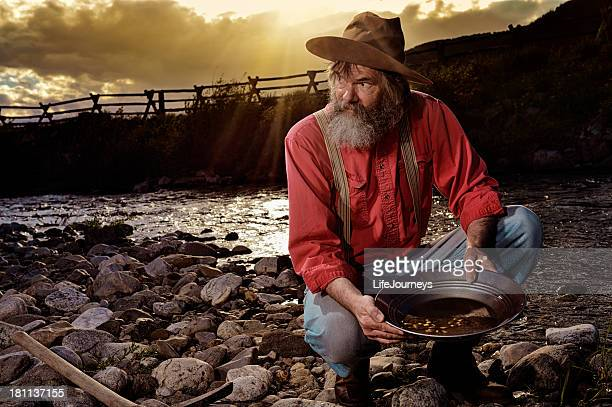Old Prospector Panning For Gold In A Western Sunset