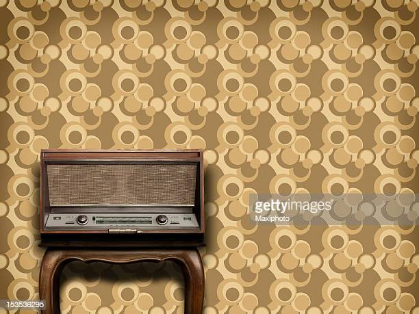 Old radio equipment on wooden table and vintage wallpaper