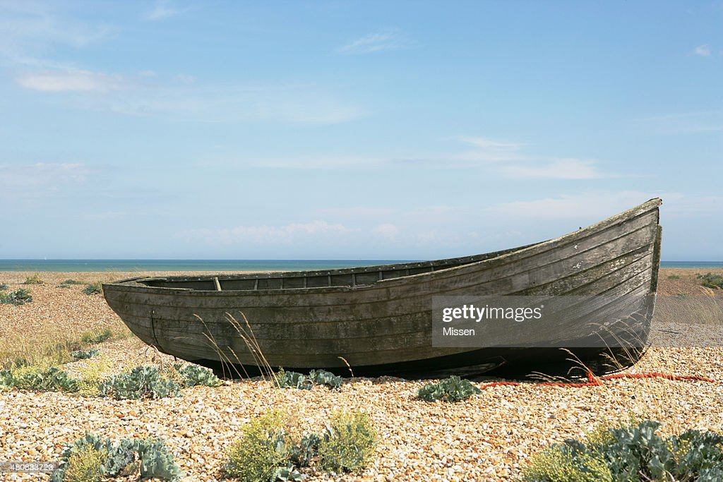 Old rowing boat on pebble beach : Stock Photo