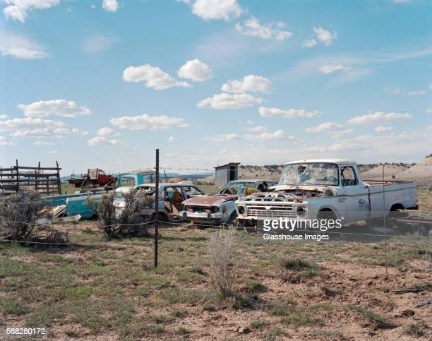 Old Rusted Cars With Bullet Holes in Windshields in Field Enclosed with Barbed Wire
