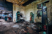 Old rusty industrial drilling machine tools in abandoned factory workshop looks like robots.