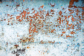 Old rusty metal wall with blue peeling paint