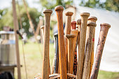 A collection of old, vintage, wooden baseball bats. Bats show some wear and an old time baseball game going on in the background.
