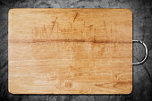 Old scratched wooden cutting board, on dark concrete texture