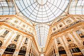 Interior with beautiful glass vaults in the famous Vittorio Emanuele shopping gallery in the center of Milan city.