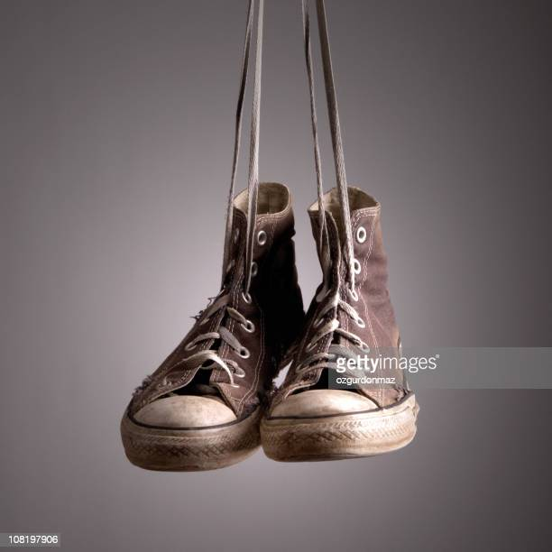 Old Sneakers Hanging by Shoelaces