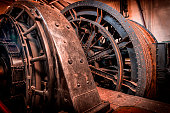Old steam engine and flywheel with steel ropes for propelling the elevator shaft in a coal mine