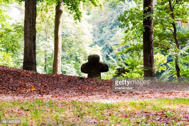 Old stone cross in the fores, background with copy space
