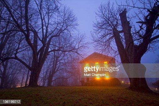 Old stone house on foggy night : Stock Photo
