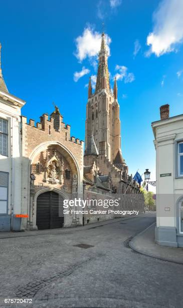 Old street in Bruges with medieval buildings and majestic Church of our Lady brick-built bell tower on background in Flanders, Belgium