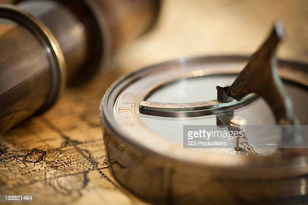 Old Style Compass and Telescope on Top of World Map