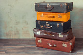 Many old suitcases stand in an empty room