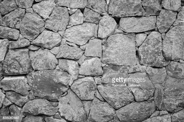 Old surrounding wall at a fortress made of stones with lichen in black and white.