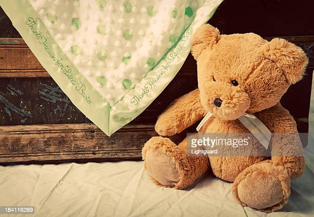 Old teddy bear near blanket-draped antique trunk