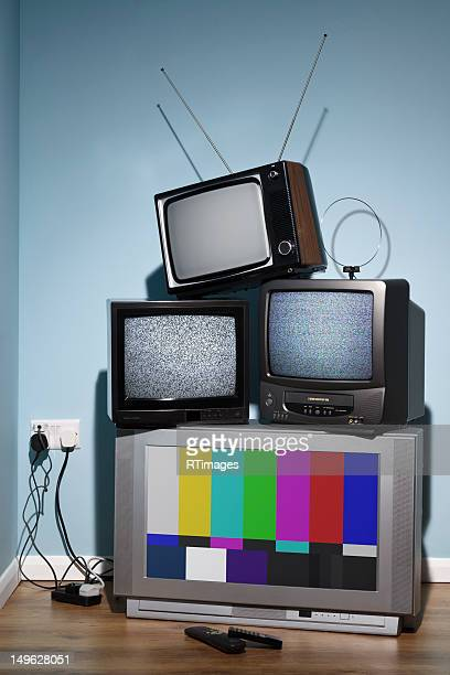 Old televisions in the corner of a room