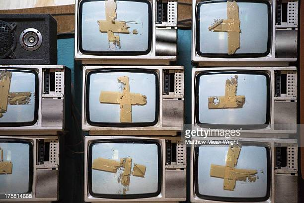 Old televisions stacked together in formation