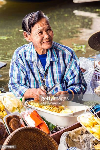 Old Thai woman selling fruit at floating market