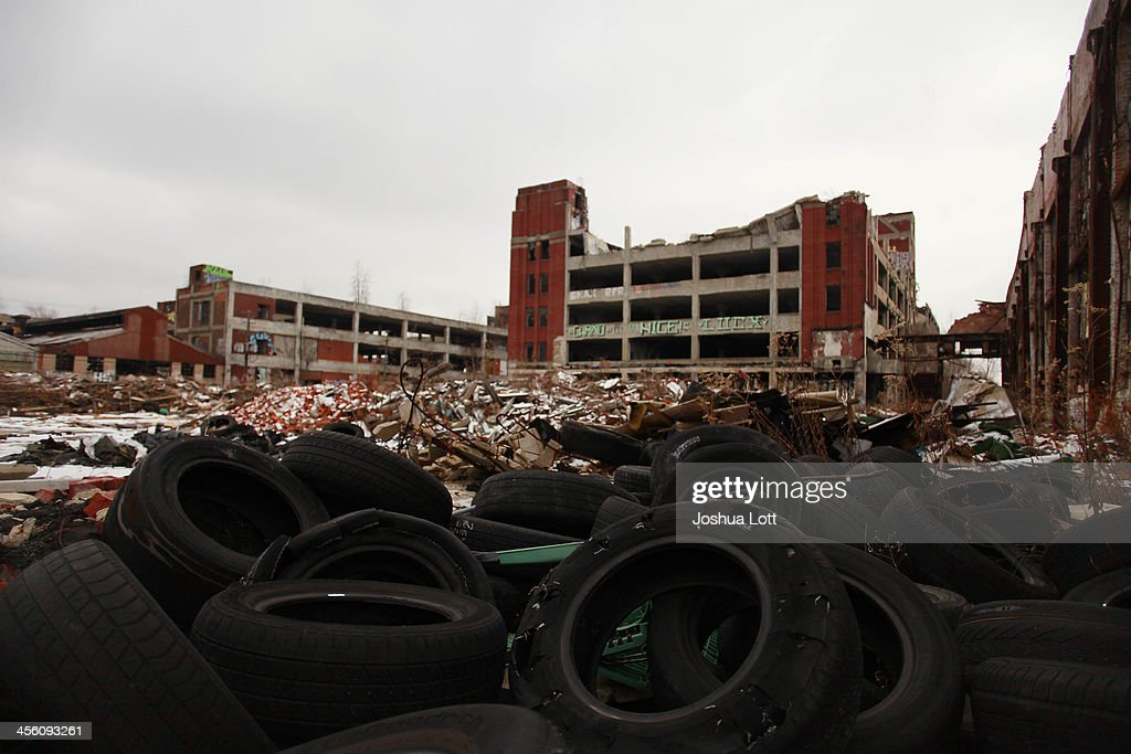 Old tires rest near the abandoned Packard Automotive Plant December 13, 2013 in Detroit, Michigan. Peru-based developer Fernando Palazuelo made his final payment on the Packard Plant, which he won during a Wayne County auction for $405,000. Palazuelo plans on developing the former automotive plant where luxury Packard cars were made in the coming years.