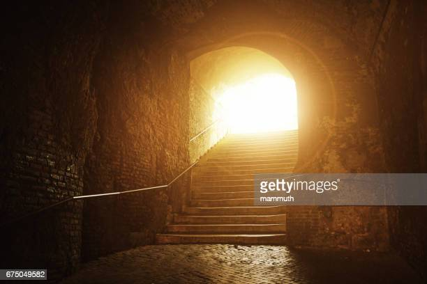 Old tunnel with stairs up to the light, Rome, Italy