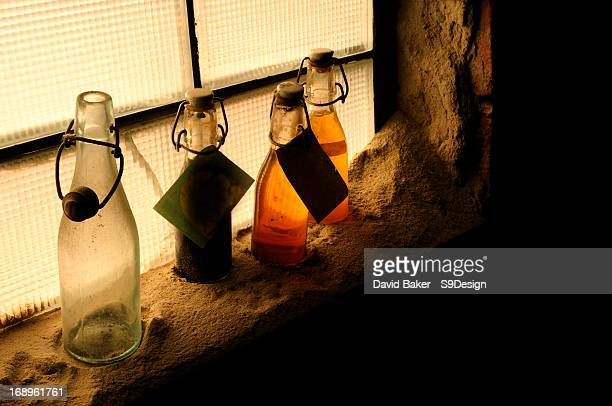Old untouched bottles in a dimly lit window