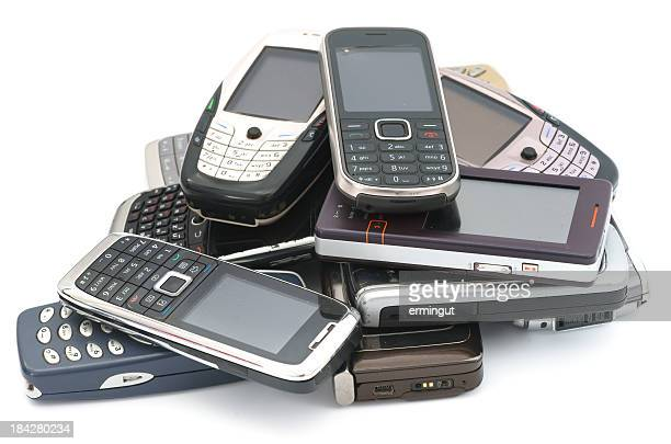 Old used cellphones pile isolated on white