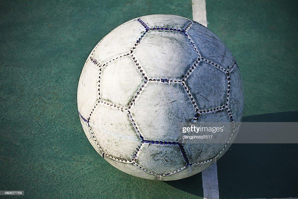 Old used football or soccer ball on cracked asphalt : Stock Photo